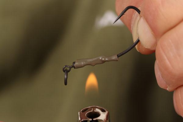 3. Nyní hadičku částečně naneseme na upínací část obratlíku tak, aby byla vidět jen část obratlíku s koncovým očkem, vezmeme do ruky zapalovač a hadičku nahřejeme. Pozor, ať se nepřepálí a pozor na prsty.